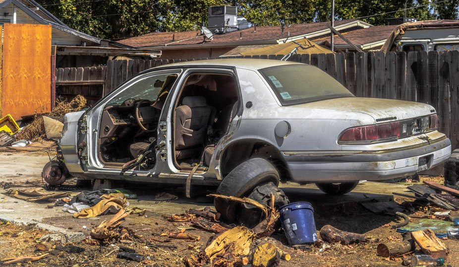 The abandoned car symbolizes the blight and despair in the neighborhood with the issues of homele...