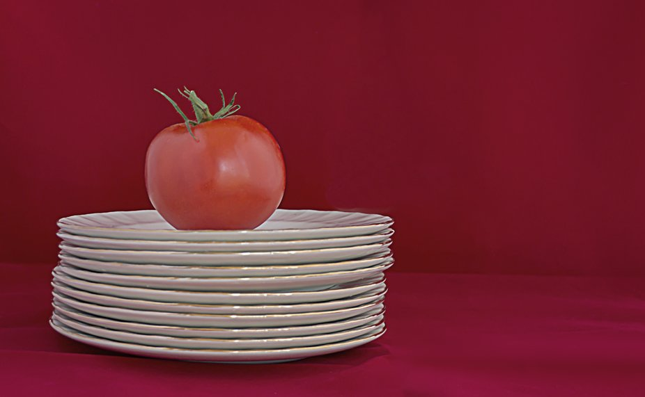 A tomato over many overlaid  white plates, on a red background