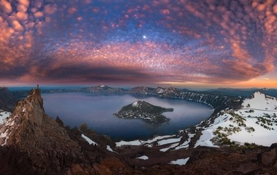 Man on hilltop viewing Crater Lake with full moon