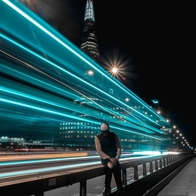 Long exposure shot on the London Bridge, capturing the light trails of an iconic double-decker bus while I am sitting still.
