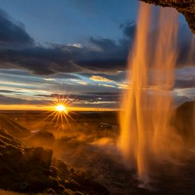 Sunset and sunburst behind the waterfall Seljalandsfoss