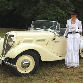 Lady in vintage costume with a cream old timer