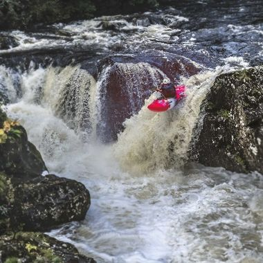 A kayak is paddled over the waterfall at Pont y Pair, Betws y Coed.