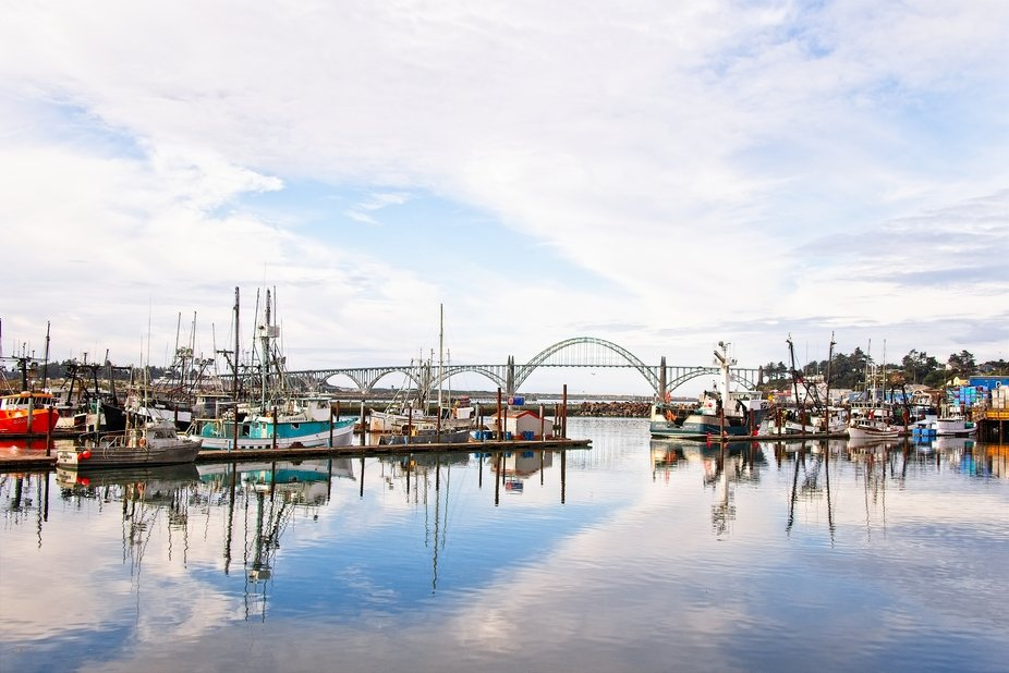Fishing boats are docked in Newport, Oregon with the Yaquina Bay Bridge in the background...