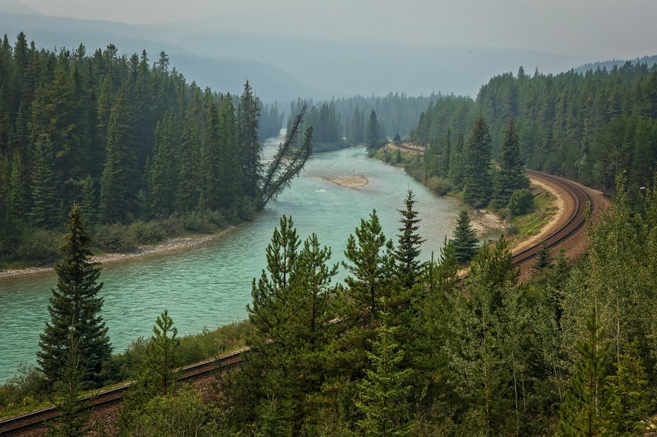 Railway tracks run along the Bow River, Alberta Canada. The mountains in the background are obscu...