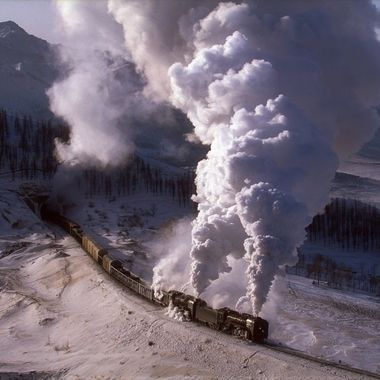 In 1995 the Mongolian Provincial authority opened a new 945 km railway line between Jining and Tongliao. Over 100 steam locomotives were purchased to operate the line.  From the town of JingPeng there was a steep climb through the mountains to the summit at Shandian then down to Reshui. Between Reshui and JingPeng there are 6 tunnels.  Winter temperatures of minus 40 were not unusual.   Here in January 1991 two QJ have just left tunnel 4.  It was more than 30 minutes walk to this location, on this morning the sun has just beaten the train to the track, the front loco is not leaking steam and the wind is right.