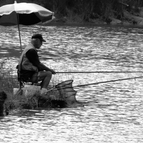 A fisherman waiting, thinking, relaxing on a river bank