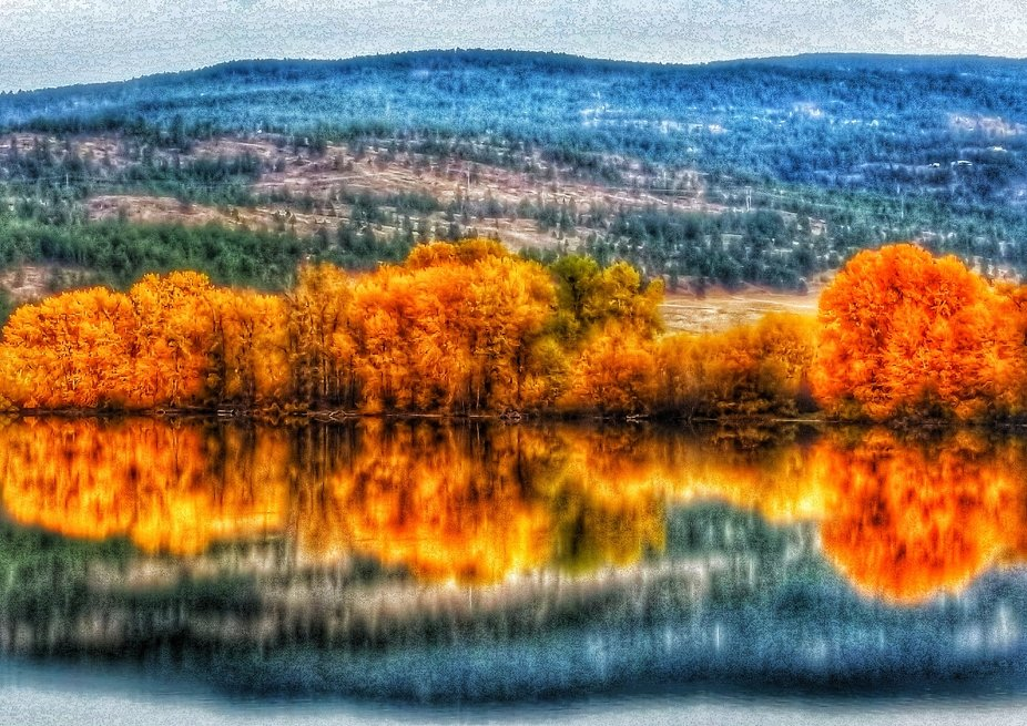 A shot across the lake showing the beauty of autumn, while reflecting itself in a liquid mirror.