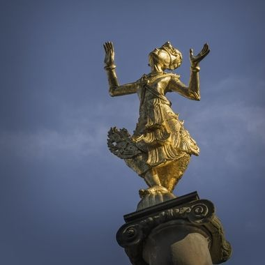 One of two golden Asian dancer figures atop plinths near the pond in the Portmeirion Village centre.
