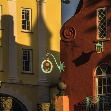 The evening sun drops in the sky over Portmeirion and the shadows of the architecture play on various surfaces.