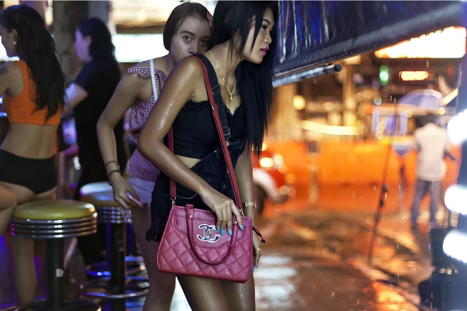 Two women seek shelter under the canopy of night club from an unexpected rain shower on Bangla Wa...