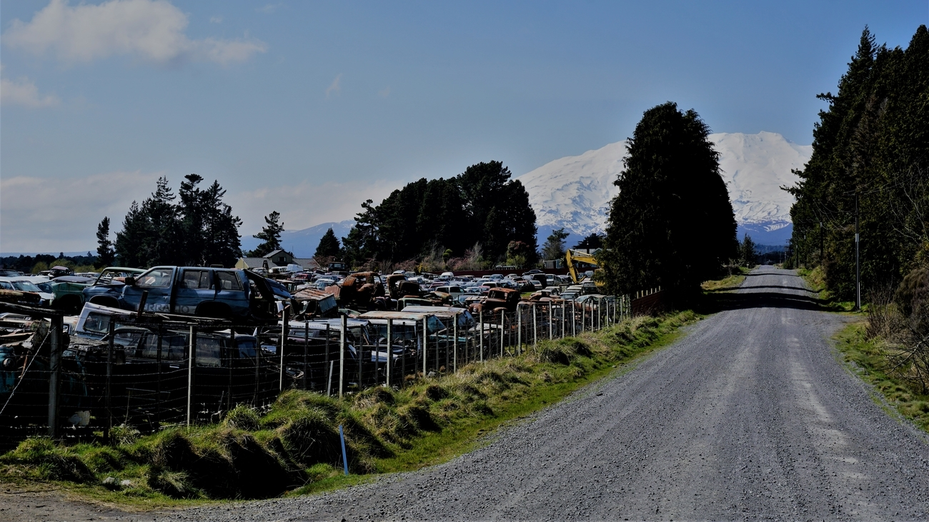 Central North Island, New Zealand, a gravel road passes through Smash Palace (Horopito) heading towards the railway line and Mt Ruapehu in the background. Smash Palace is where the end scenes of The Hunt for the Wilderpeople were filmed and is a vast junkyard of old and recent car frames, chassis, and parts
