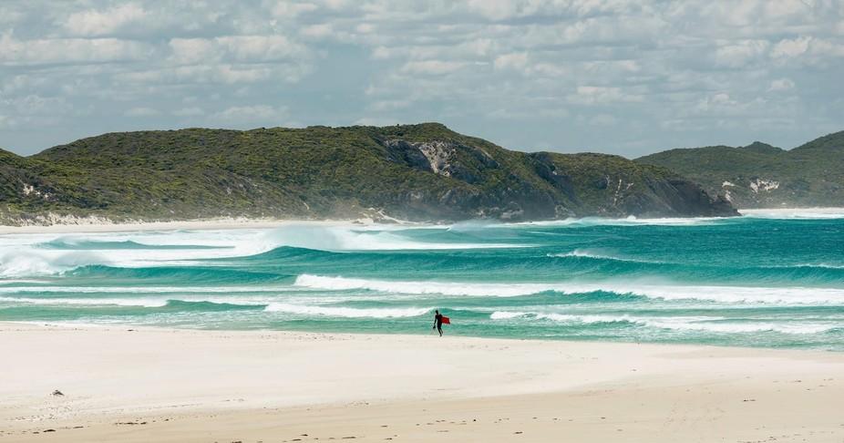Lone surfer seeking the perfect ride