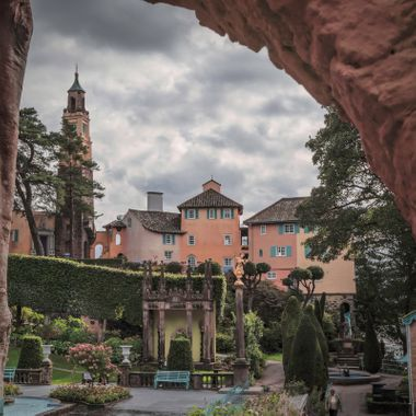A view of Portmeirion buildings through a wall arch.
