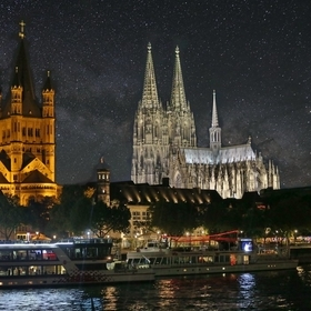 The lights of Cologne, Germany with the Cologne Cathedral towering over the city. The tower of Gross St. Martin Church is on the left, and the Mi...