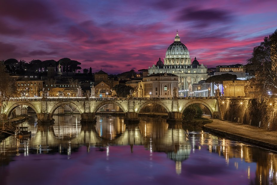 View of St. Peter's Basilica in the Vatican and Sant'Angelo bridge at sunset