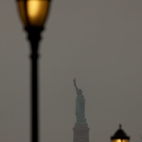 Framed by lightposts, the Statue of Liberty stands tall in the distance.