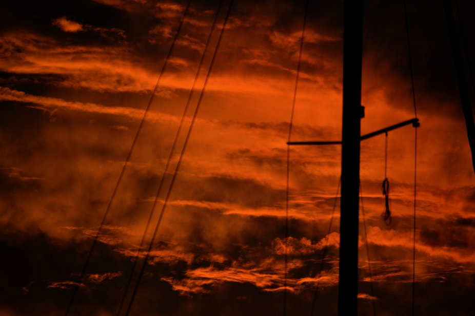 Beautiful sunsets covered by clouds with sailboats rigging and masts silhouetted
