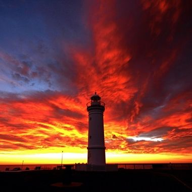 Sunrise at Kiama Lighthouse with the sky ablaze with red.