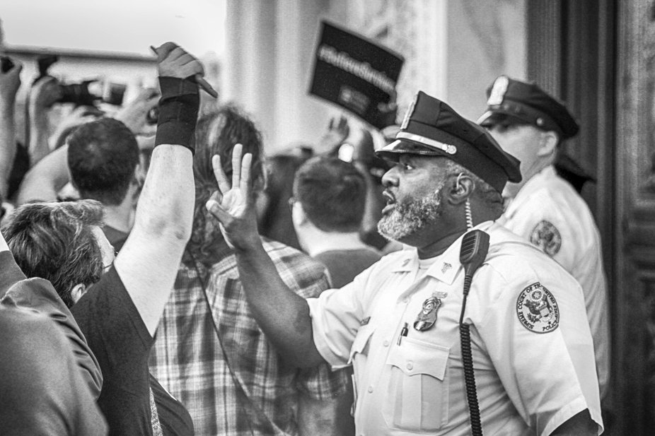 A US Supreme Court Police Officer communicates with the demonstrators.