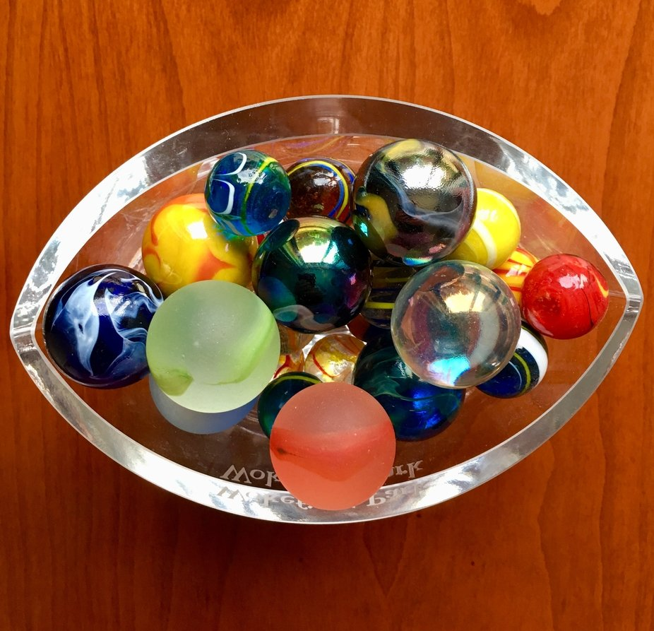 Still life shot of marbles in a glass container.