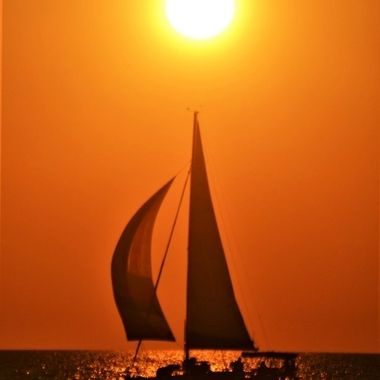 Sailboat underway passing under the setting sun in Nokomis, FL