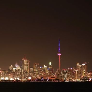 Shot from across the Humber Bay, the Toronto nighttime skyline in winter is a medly of colours and steam....