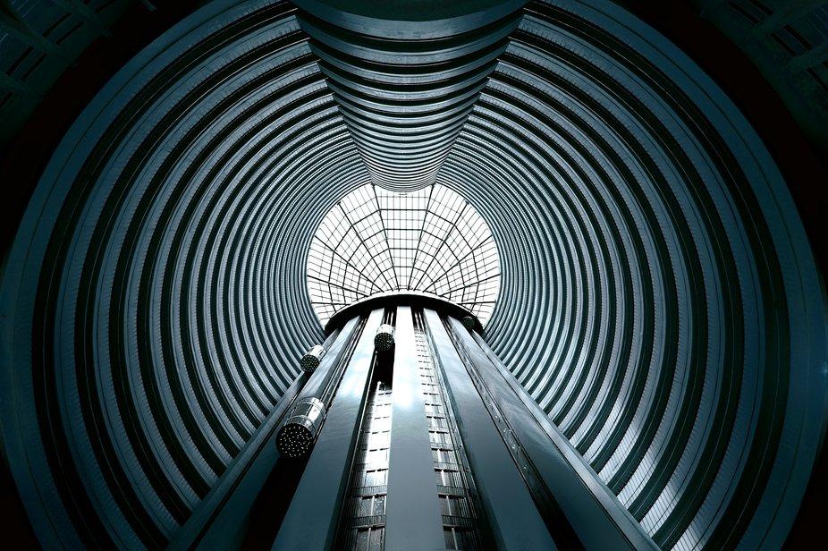 Soaring upwards in an elevator module inside a hotel atrium in downtown Singapore