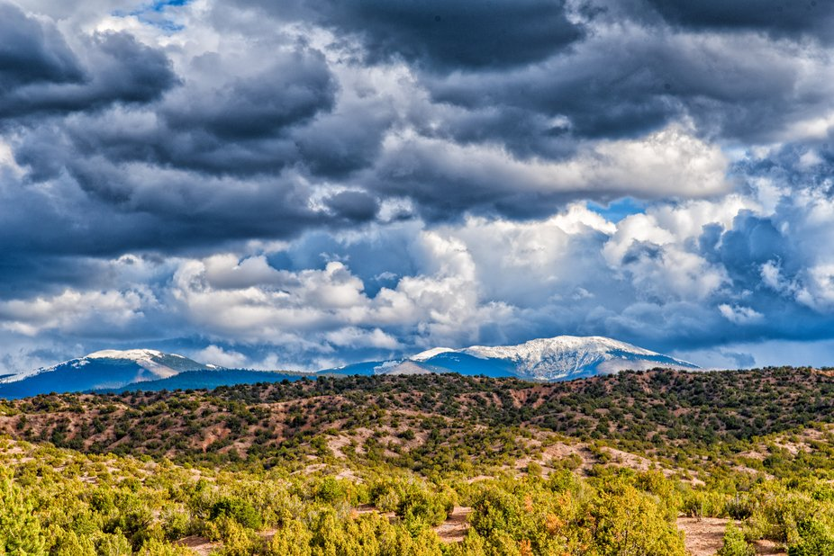 High sun pierced mixed storm clouds along rural New Mexico Route 503 with the Sangre de Cristo Mo...