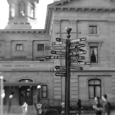 The distance sign in Pioneer Courthouse Square in Portland, Oregon with Pioneer Courthouse in the background. Taken with a Canon 80D and Lensbaby Composer Pro II with Sweet 35 front optic.