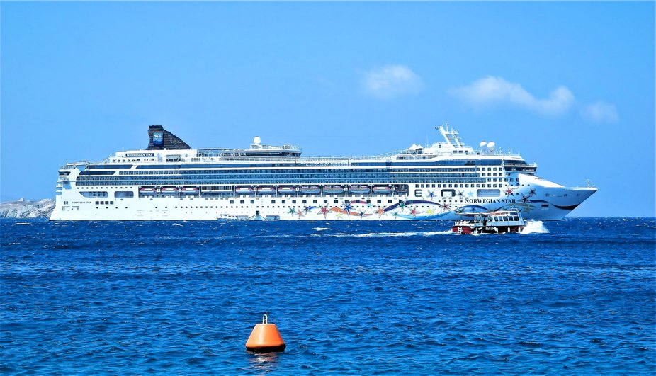 Our cruise ship in the port of Mykonos Island Greece. Passengers in a tender returning to the ship.