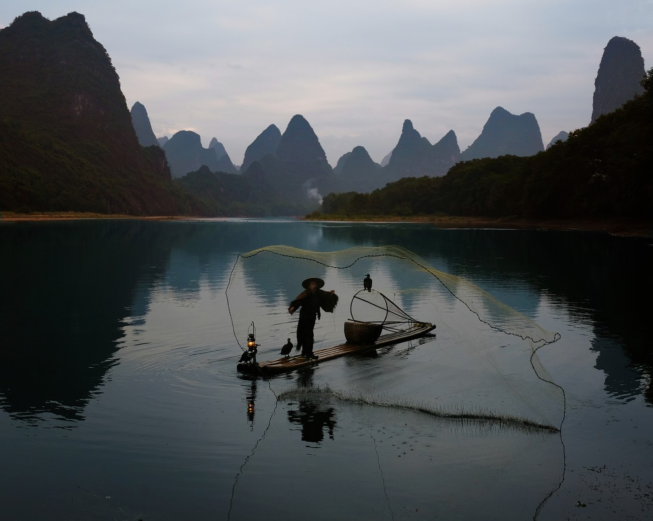 Cormorant fisherman throwing his net into Li river