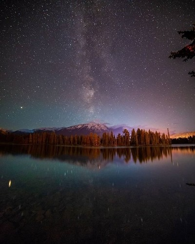 The Milky Way and mountains. Stars above and below at Lake Beauvert and Jasp
