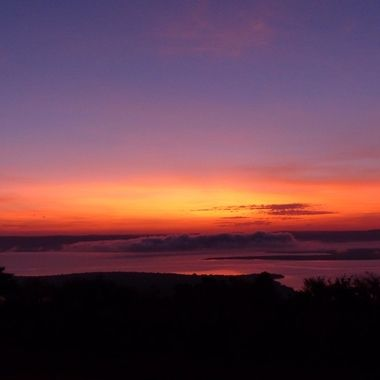 A very unusual sunrise over lake Ihema in Akagera Nationla Park, Rwanda with a mist bank over the lake