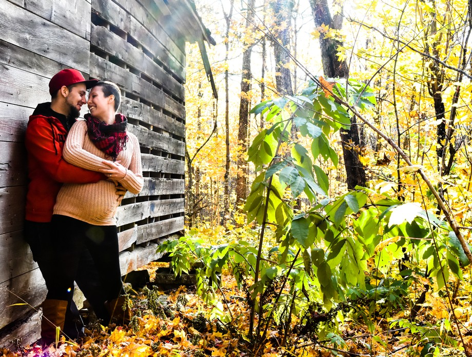 A men with a pregnant girl in love next to a old hut in the middle of the forest.