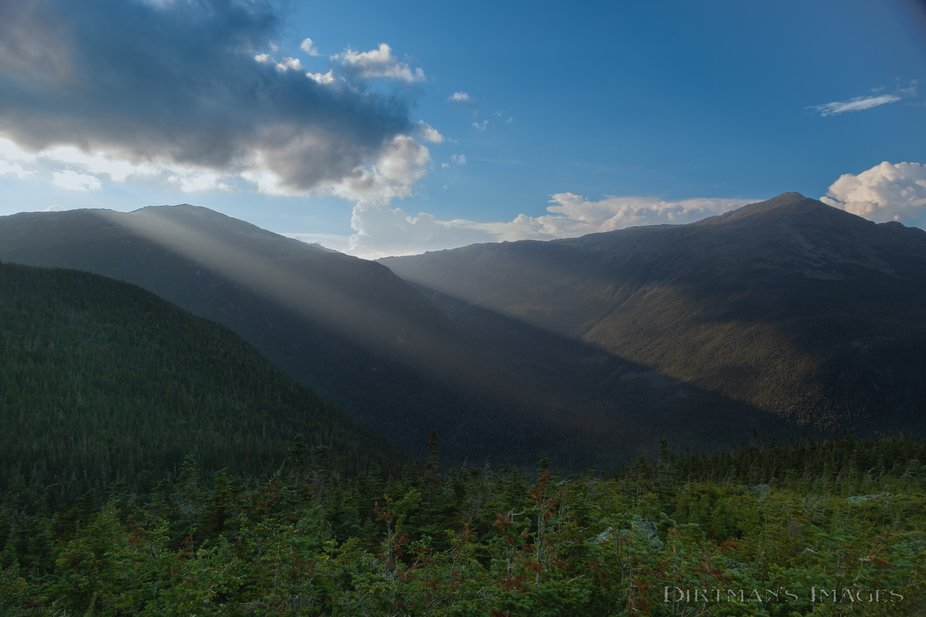 Rays of sunlight beam through breaks of the clouds by Mount Adams and illuminate the spurs of Mou...
