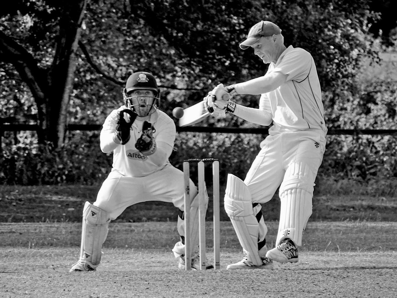 Batsman cutting a shot as wicketkeeper looks on