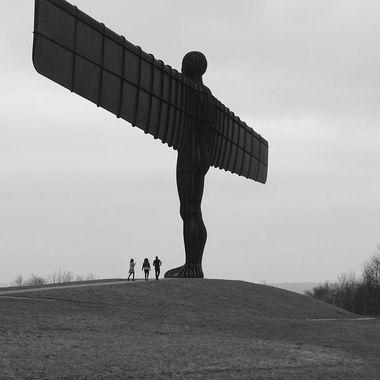 Three people visiting Antony Gormley's Angel of the North at Gateshead