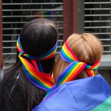 Couple wearing rainbow bandanas at Leeds Pride march