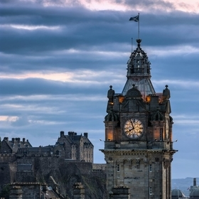 Detail shot on Balmoral Hotel with Edinburgh Castle in the background on sunset. Taken at the famous lookout on Calton Hill overviewing the old c...