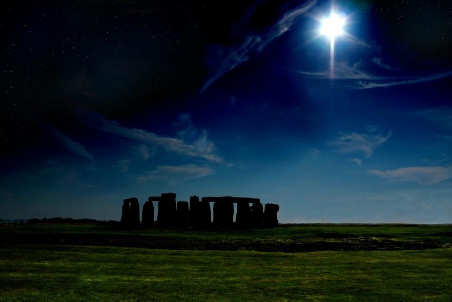 Silhouette of Stonehenge on the Salisbury Plain with sun and stars.