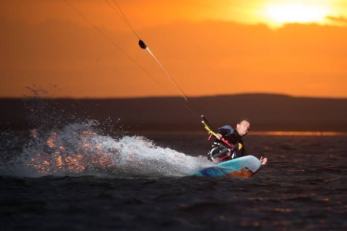 """Thierry Schmitter is a kitesurfer who's not stopped by sitting in a wheelchair, his skills are impressive! He straps himself to a seat mounted to his kiteboard (""""sit-kite""""). We attached a flash to the lines for an evening session on the water in the """"Zandmotor"""", The Hague, the Netherlands. It was fun, we only stopped when it was too dark to focus the camera."""