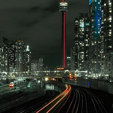 Shot from the Bathurst street bridge - the CN Tower plays central role in this image.  The leading lines of the tracks and train's tail lights help to draw the eye to the tower's base.