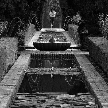 Mono image of girl taking a photo of the Alhambra Garden fountains