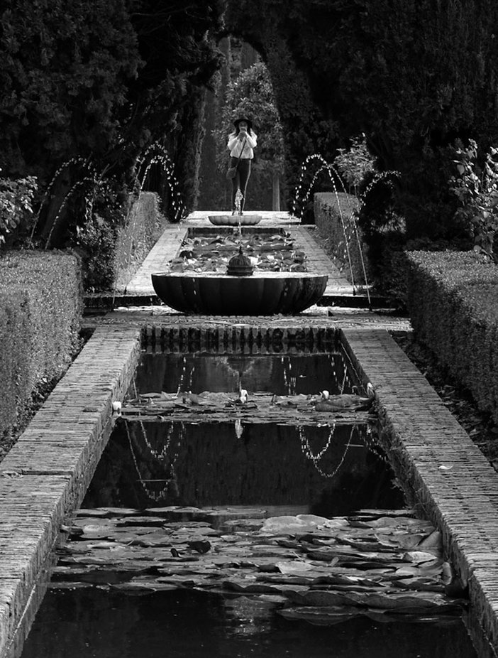 Mono image of girl taking a photo of the Alhambra Garden fountains