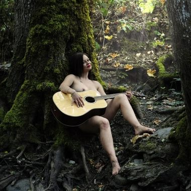 Samantha playing her guitar at Lithia Creek in the nude.