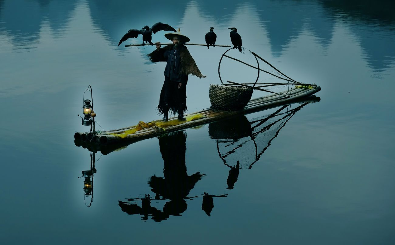 Cormorant fisherman with his birds reflected into the Li river