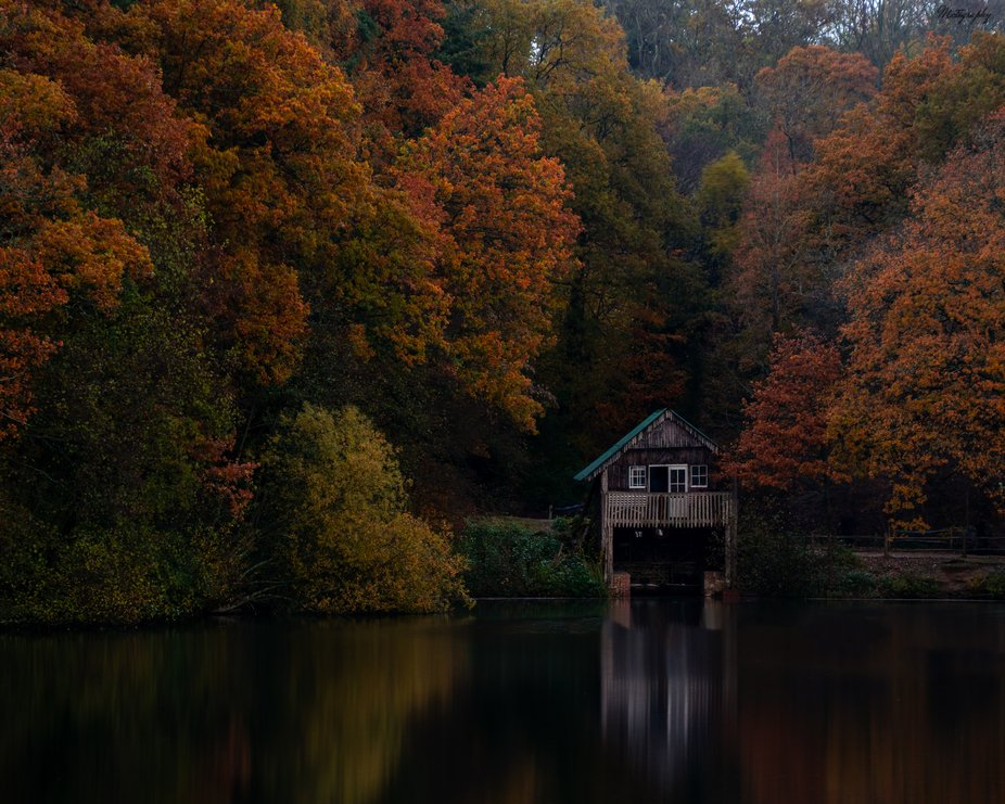 Boat house at Winkworth with an autumn colour backdrop