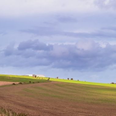 This was taken on a stormy day. When the sun managed to get through the clouds it cast some lovely light on the fields.  This is a view that I photograph often and enjoy its various moods.