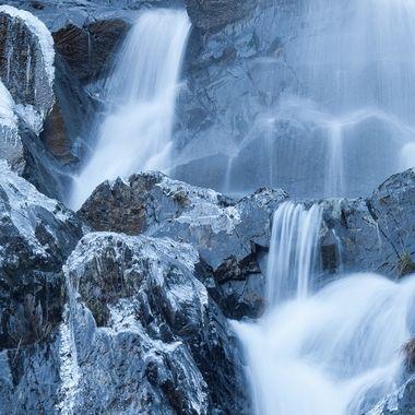 Rio de montaña.Temperatura bajo cero.El agua en movimiento no se hiela pero el agua que moja las rocas,si.